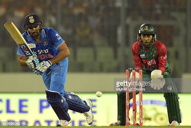 Indian cricketer Rohit Sharma is watched by Bangladesh wicketkeeper Mushfiqur Rahim as he plays a shot during a Twenty20 cricket match between India...