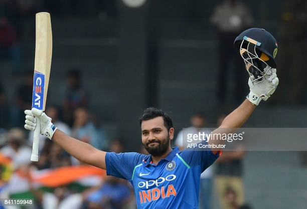 Indian cricketer Rohit Sharma raises his bat and helmet in celebration after scoring a century during the fourth one day international cricket match...