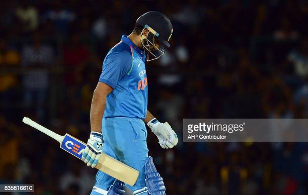Indian cricketer Rohit Sharma walks back to the pavilion after his dismissal during the first One Day International cricket match between Sri Lanka...