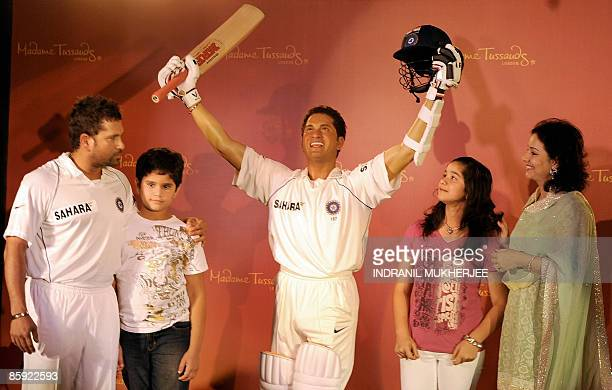 Indian cricketer Sachin Tendulkar along with his son Arjun daughter Sara and wife Anjali poses with his waxwork figure at the unveiling ceremony in...
