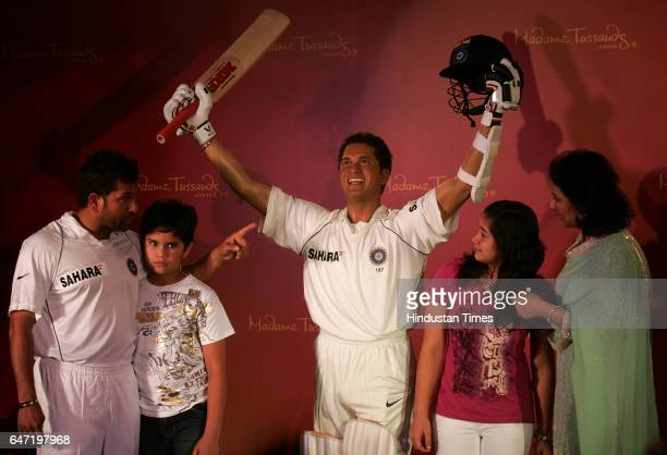 Indian Cricketer Sachin Tendulkar and his family son Arjun daughter Sara and wife Anjali pose with his wax statue made by Madame Tussaud museum at...