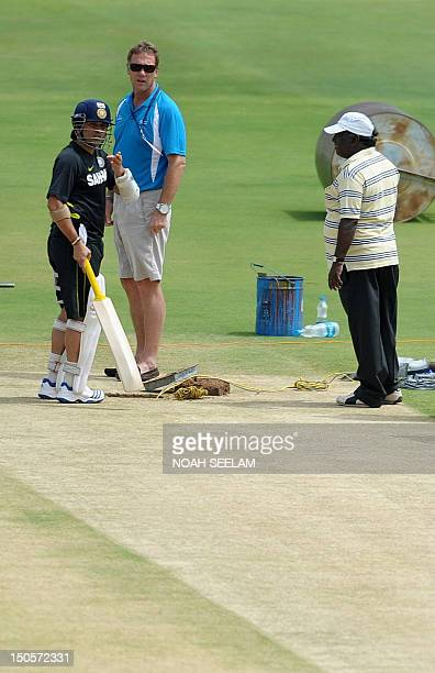 Indian cricketer Sachin Tendulkar and match referee Chris Broad check the pitch along with curator Chandra Sekhar during a training session at the...