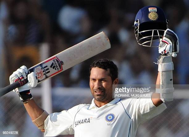 Indian cricketer Sachin Tendulkar celebrates after reaching his century on the fifth day of the first test between India and Sri Lanka at the Motera...