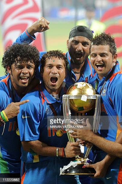 Indian cricketer Sachin Tendulkar celebrates with teammates as he holds the trophy after beating Sri Lanka in the ICC Cricket World Cup 2011 final...
