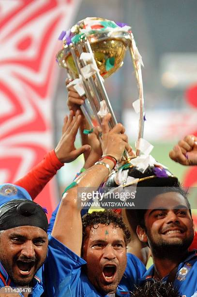 Indian cricketer Sachin Tendulkar celebrates with the trophy after beating Sri Lanka in the ICC Cricket World Cup 2011 final match at The Wankhede...