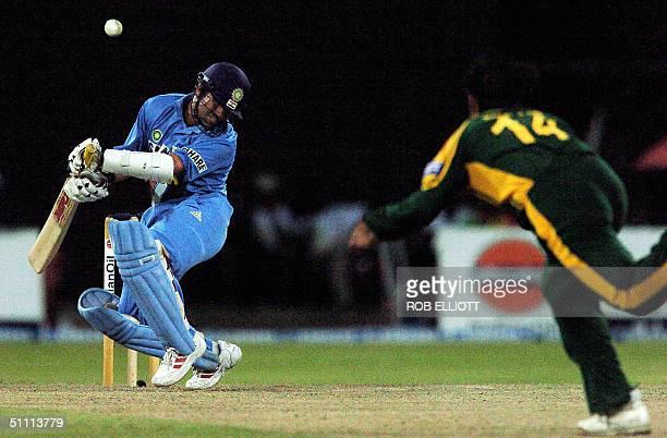 Indian cricketer Sachin Tendulkar ducks his head as he receives a bouncer from Pakistani bowler Shoaib Aktar during the Asia Cup match between India...
