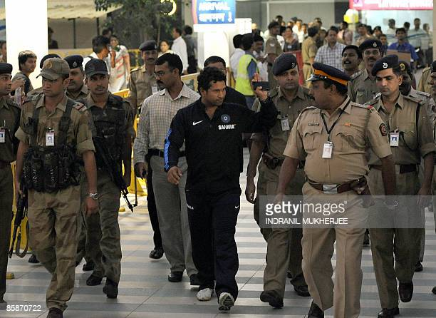 Indian cricketer Sachin Tendulkar gestures to supporters as he walks out of the city airport after arriving from New Zealand in Mumbai late April 8...