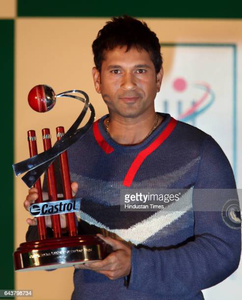 Indian cricketer Sachin Tendulkar holds a trophy after winning the 'Castrol Indian Cricketer of the Year' award during a function in Mumbai