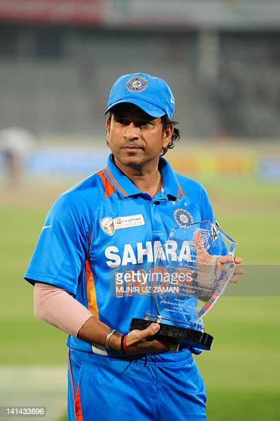 Indian cricketer Sachin Tendulkar holds a trophy for his 100 international centuries on March 16 2012 following the one day international Asia Cup...