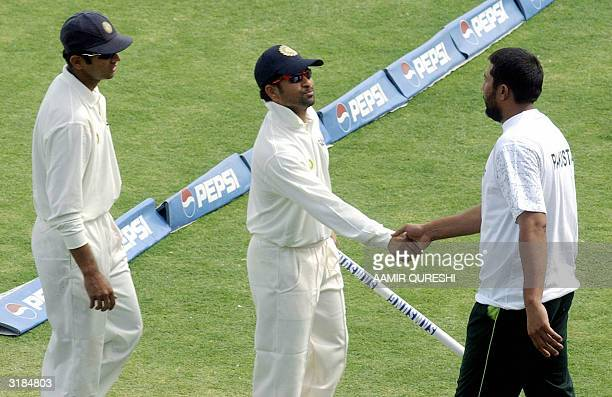 Indian cricketer Sachin Tendulkar is congratulated by Pakistani captain Inzamam-ul Haq as Rahul Dravid looks on following India's victory over...