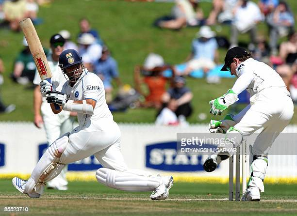 Indian cricketer Sachin Tendulkar plays a shot as New Zealand wicket keeper Drendon McCullum attempts to stop the ball during the third day of the...