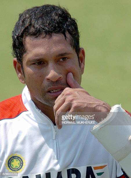 Indian cricketer Sachin Tendulkar wipes swet drops as he walks back to the shade during a practice session at the Keenan Stadium in Jamshedpur 08...