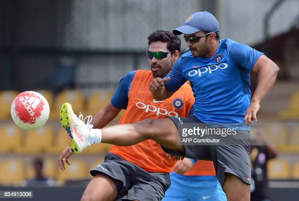 Indian cricketer Shardul Thakur plays football with teammate Bhuvneshwar Kumar during a practice session at the Rangiri Dambulla International...