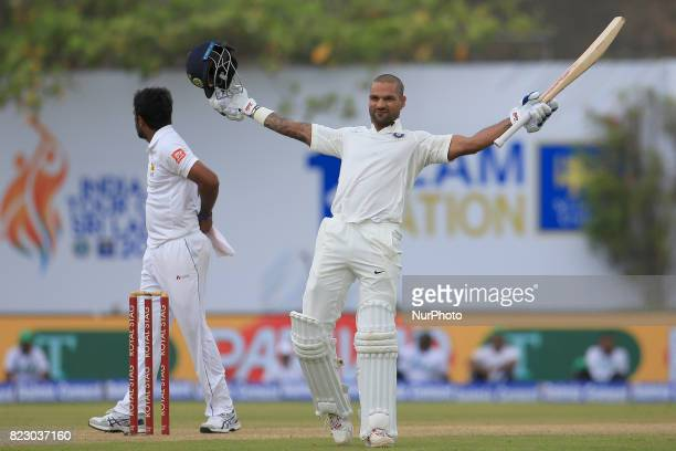 Indian cricketer Shikhar Dhawan celebrates after scoring 100 runs during the 1st Day's play in the 1st Test match between Sri Lanka and India at the...