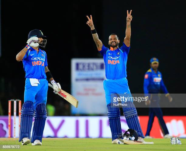 Indian cricketer Shikhar Dhawan celebrates after scoring hundred runs as Indian captain Virat Koli looks on during the 1st One Day International...