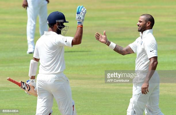 Indian cricketer Shikhar Dhawan is congratulated by his teammate Cheteshwar Pujara after he scored a century during the first day of the third and...
