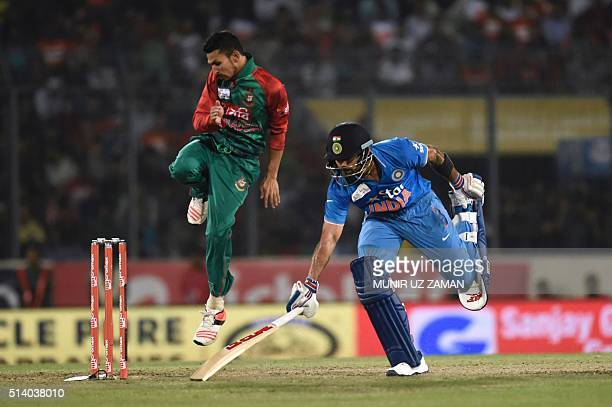 Indian cricketer Shikhar Dhawan makes his ground as Bangladeshi cricketer Nasir Hossain reacts during the Asia Cup T20 cricket tournament final match...