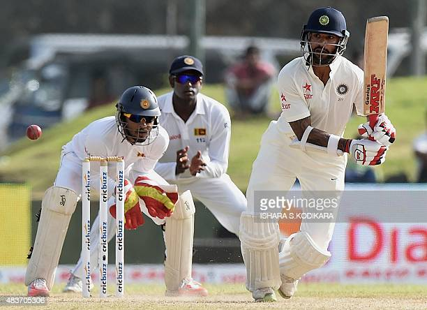 Indian cricketer Shikhar Dhawan plays a shot as Sri Lankan wicketkeeper Dinesh Chandimal and Sri Lankan cricket captain Angelo Mathews look on during...
