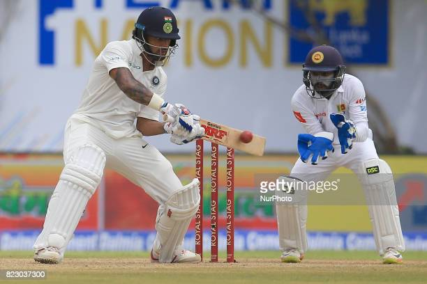 Indian cricketer Shikhar Dhawan plays a shot during the 1st Day's play in the 1st Test match between Sri Lanka and India at the Galle International...