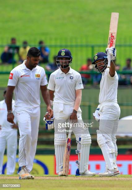 Indian cricketer Shikhar Dhawan raises his bat after scoring 50 runs with his partner Lokesh Rahul during the 1st Day's play in the 3rd Test match...