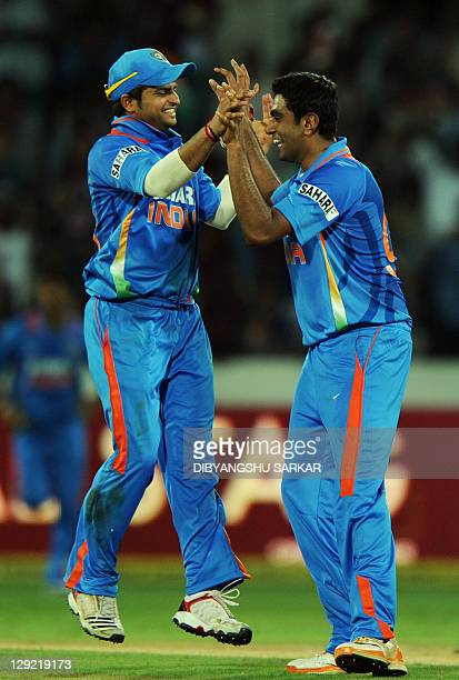 Indian cricketer Suresh Raina congratulates teammate Ravichandran Ashwin for taking the wicket of unseen England batsman Ravi Bopara during the first...