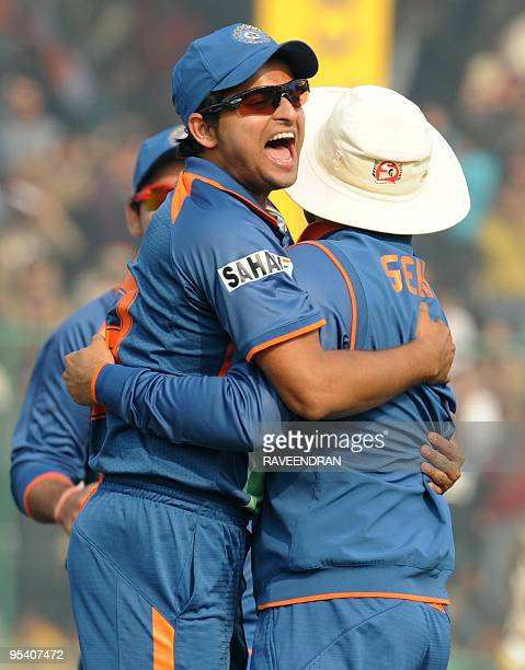 Indian cricketer Suresh Raina embraces teammate Virender Sehwag as they celebrate the dismissal of unseen Sri Lankan batsman Thilan Samaraweera...