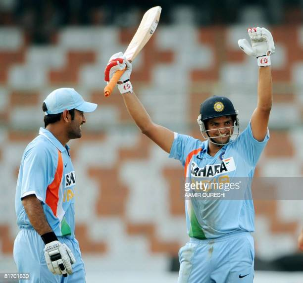 Indian cricketer Suresh Raina raises his bat after he scored a century against Hong Kong as team captain Mahendra Singh Dhoni looks on during a Group...