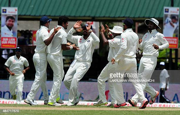 Indian cricketer Umesh Yadav celebrates with teammates after dismissing Sri Lankan cricketer Dimuth Karunaratne during the second day of their second...