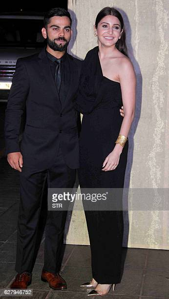 Indian cricketer Virat Kohli and actress Anushka Sharma pose for a photograph during designer Manish Malhotra's 50th birthday in Mumbai on December 5...
