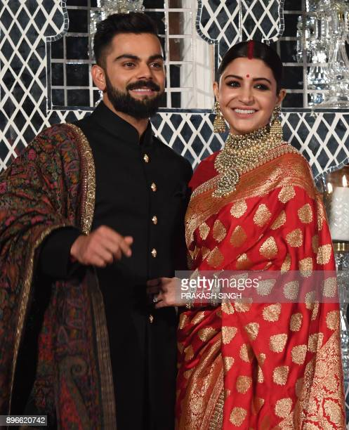 Indian cricketer Virat Kohli and Bollywood actress Anushka Sharma who were recently married in Italy pose during a reception in New Delhi on December...