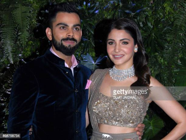 Indian cricketer Virat Kohli and his wife Bollywood actress Anushka Sharma pose during their wedding reception in Mumbai on December 26 2017 They...