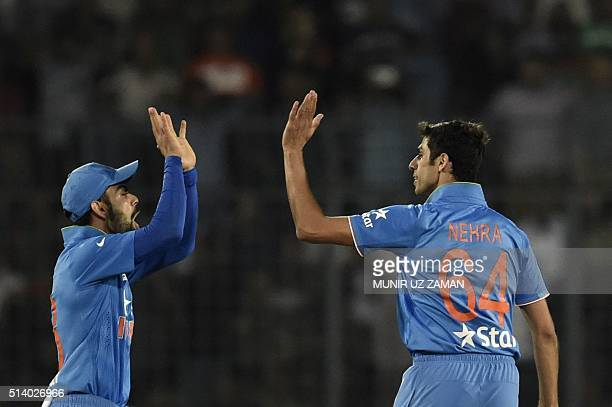 Indian cricketer Virat Kohli celebrates with his teammate Ashish Nehra after the dismissal of the Bangladeshi cricketer Soumya Sarkar during the Asia...