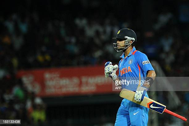Indian cricketer Virat Kohli raises his bat to acknowledge the crowd after his half century during the ICC Twenty20 Cricket World Cup Super Eight...
