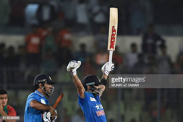 Indian cricketer Virat Kohli reacts next to the captain Mahendra Singh Dhoni after winning the match during the Asia Cup T20 cricket tournament final...
