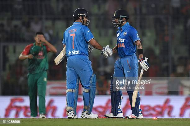 Indian cricketer Virat Kohli shakes hand with captain Mahendra Singh Dhoni after winning the match during the Asia Cup T20 cricket tournament final...