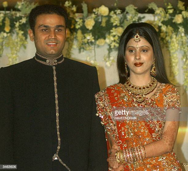 Indian cricketer Virender Sehwag and new wife Aarti Ahlawat pose for photographers at their wedding reception in New Delhi 24 April 2004 The pair...