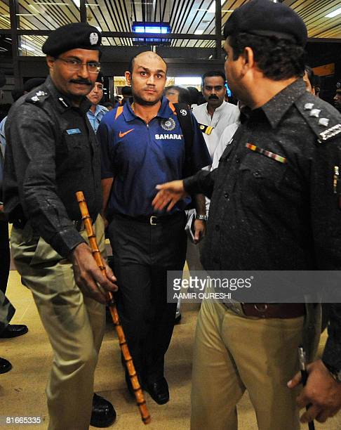 Indian cricketer Virender Sehwag is escorted by Pakistani police officials upon his arrival at the Jinnah International airport in KarachiPakistan on...