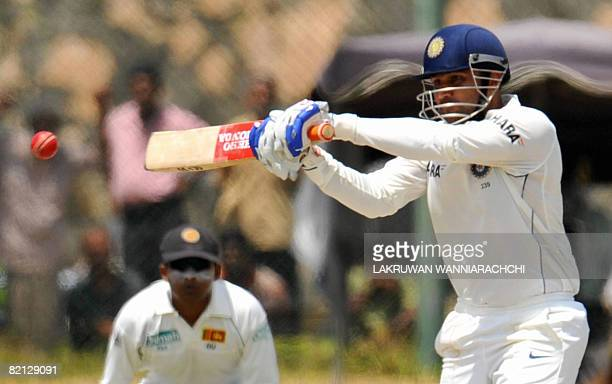 Indian cricketer Virender Sehwag is watched by Sri Lankan captain Mahela Jayawardene as he bats during the first day of the second Test match between...