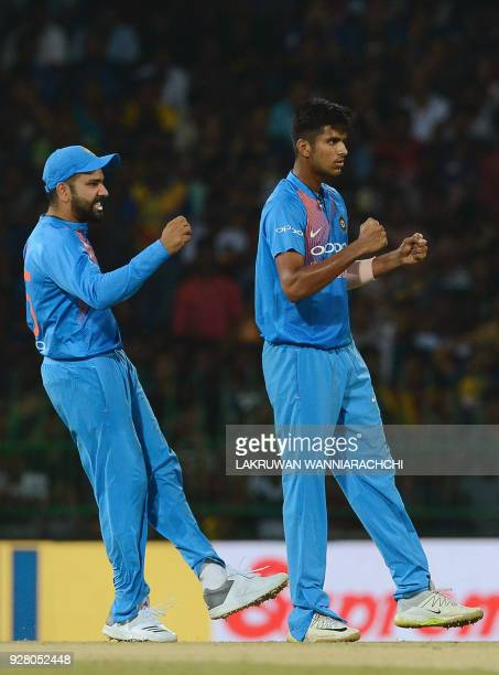 Indian cricketer Washington Sundar celebrates with captain Rohit Sharma after he dismissed Sri Lankan cricketer Kusal Mendis during the opening...