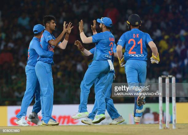 Indian cricketer Washington Sundar celebrates with his teammates after he dismissed Sri Lankan cricketer Kusal Mendis during the opening Twenty20...