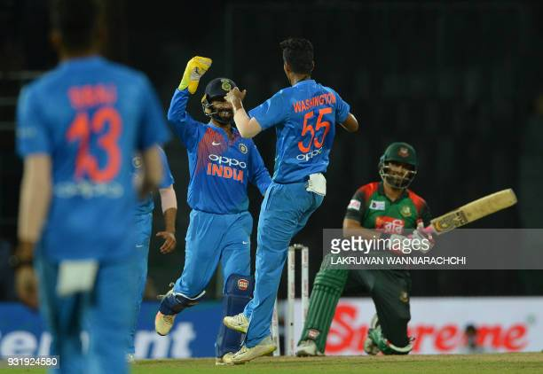 Indian cricketer Washington Sundar celebrates with wicketkeeper Dinesh Karthik after he dismissed Bangladesh cricketer Tamim Iqbal during the fifth...