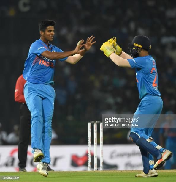 Indian cricketer Washington Sundar celebrates with wicketkeeper Dinesh Karthik after dismissing Sri Lankan cricketer Kusal Perera during the fourth...