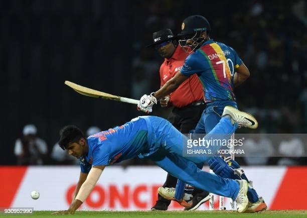 Indian cricketer Washington Sundar stops the ball as Sri Lankan cricketer Danushka Gunathilaka looks on during the fourth Twenty20 international...