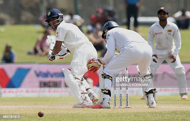 Indian cricketer Wriddhiman Saha plays a shot as Sri Lankan wicketkeeper Dinesh Chandimal and Kaushal Silva look on during the second day of the...