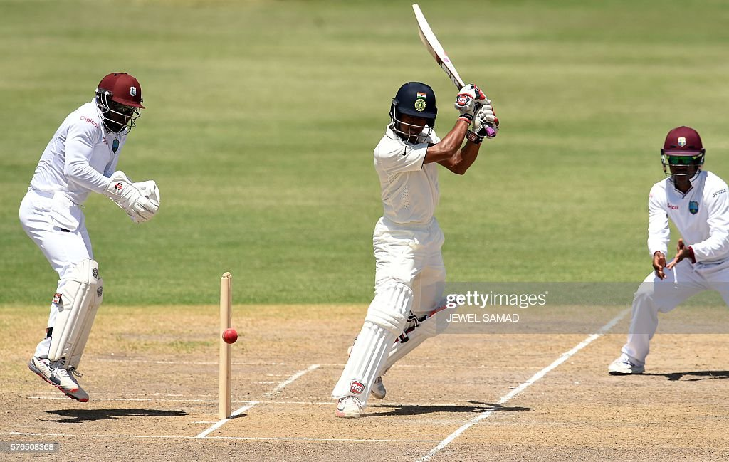 Indian cricketer Wriddhiman Saha plays a shot during Day 2 of the three-day tour match between India and WICB President's XI squad at the Warner Park stadium in Basseterre, Saint Kitts, on July 15, 2016. / AFP / Jewel SAMAD