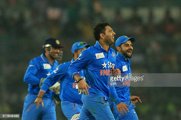Indian cricketer Yuvraj Singh celebrates with his teammates after the dismissal of Pakistan cricket captain Shahid Afridi during the match between...