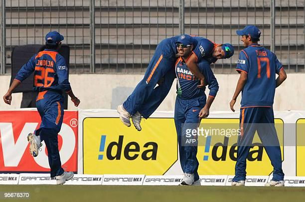 Indian cricketer Yuvraj Singh lifts his team mate Suresh Raina as cricketers Ravindra Jadeja and Sudeep Tyagi look on after the dismissal of Sri...