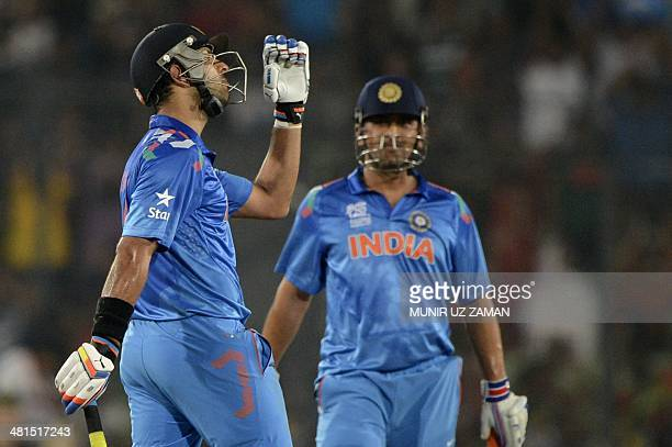 Indian cricketer Yuvraj Singh reacts after scoring a half century as his captain Mahendra Singh Dhoni looks on during the ICC World Twenty20...