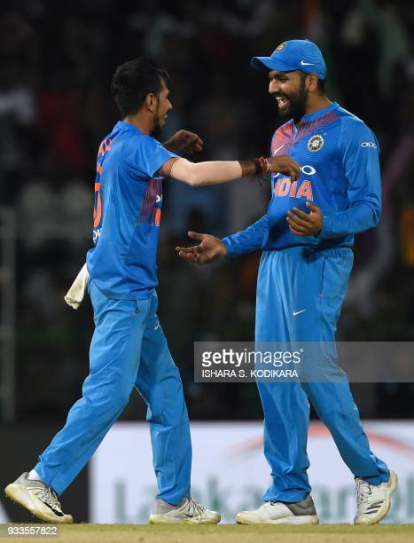 Indian cricketer Yuzvendra Chahal and team captain Rohit Sharma celebrate after the dismissal of Bangladeshi cricketer Soumya Sarkar during the final...