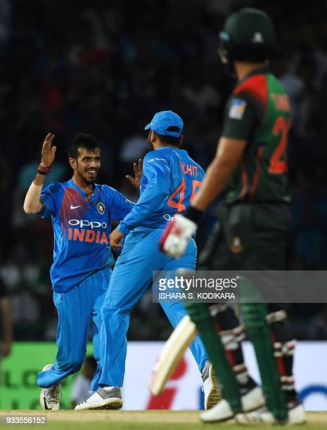 Indian cricketer Yuzvendra Chahal celebrates with a teammate after he dismissed Bangladeshi cricketer Tamim Iqbal during the final Twenty20...